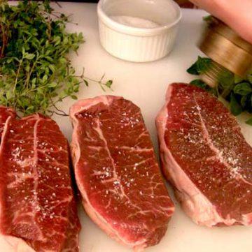 seasoning steak with salt and pepper